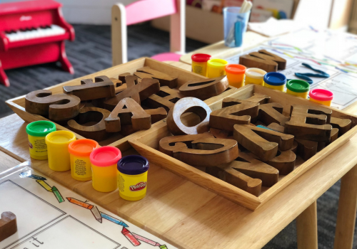 craft table with play-doh and cardboard letters in a bin